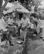 Men drinking sorgam beer in the shade of a tree- West Nile, Moyo District, Uganda.