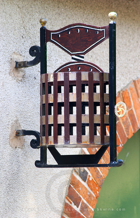 A wrought iron painted sign that illustrates the theme of champagne and wine production: a traditional vertical basket wine press, the village of Hautvillers in Vallee de la Marne, Champagne, Marne, Ardennes, France