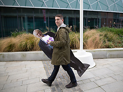 © Licensed to London News Pictures . 25/09/2016 . Liverpool , UK.  A man carrying a cardboard cutout of Labour Party leader Jeremy Corbyn walking towards the ACC in Liverpool Docks , on the first day of the Labour Party Conference . Photo credit : Joel Goodman/LNP