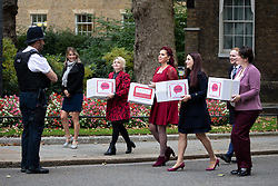 © Licensed to London News Pictures. 08/10/2018. London, UK. Natasha Devon MBE and Luciana Berger MP, (4L, 5L) and other supporters of the 'Where's Your Head At?' campaign deliver a petition to Downing Street, calling for a change in the law, to give mental health equal importance to physical health in the workplace. Photo credit : Tom Nicholson/LNP