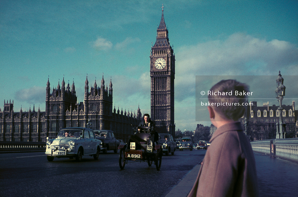 A young boy watches classic and vintage cars driving over Westminster Bridge and under Big Ben as part of the RAC London to Brighton Car Rally, in the winter of 1971, on 7th November 1971, in London, England,