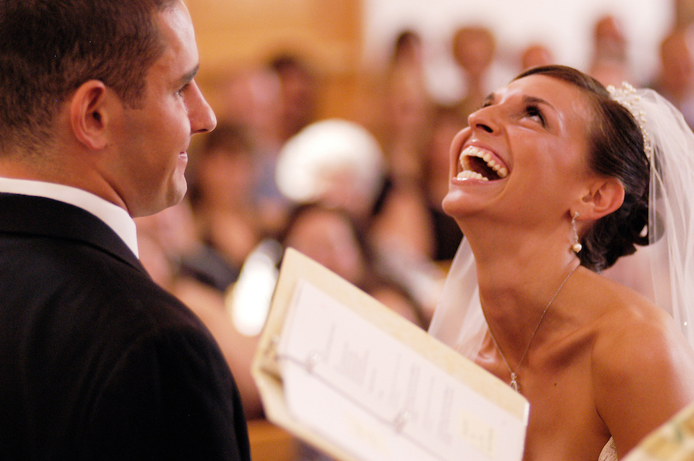 """Groom sneaks a kiss before """"the kiss"""" and gets a laugh."""