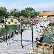 Tourists on the bridge at the main entrance at the Imperial City in Hue, Vietnam. A self-enclosed and fortified palace, the complex includes the Purple Forbidden City, which was the inner sanctum of the imperial household, as well as temples, courtyards, gardens, and other buildings. Much of the Imperial City was damaged or destroyed during the Vietnam War. It is now designated as a UNESCO World Heritage site.