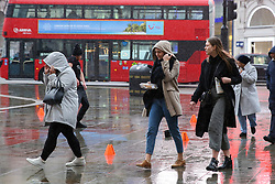 © Licensed to London News Pictures. 06/03/2019. London, UK. Tourists shelter from the rain beneath under hoods as it starts raining in the capital. Photo credit: Dinendra Haria/LNP
