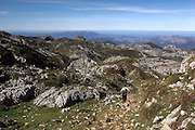 A man hikes down from the Collada el Jito viewpoint in the Picos de Europa national park with his dog
