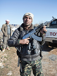 © Licensed to London News Pictures. 11/12/2014. Sinjar Mountains, Iraq. A Yazidi member of the Iraqi-Kurdish peshmerga shows off his rifle, scrubbed to remove any sign of bluing, at a peshmerga base on the top of Mount Sinjar.<br /> <br /> Although a well publicised exodus of Yazidi refugees took place from Mount Sinjar in August 2014 many still remain on top of the 75 km long ridge-line, with estimates varying from 2000-8000 people, after a corridor kept open by Syrian-Kurdish YPG fighters collapsed during an Islamic State offensive. The mountain is now surrounded on all sides with winter closing in, the only chance of escape or supply being by Iraqi Air Force helicopters. Photo credit: Matt Cetti-Roberts/LNP
