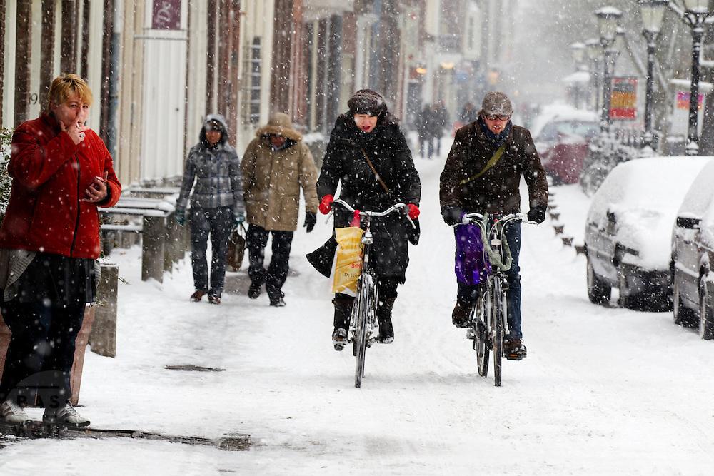 Een vrouw steekt buiten het café op de Oudegracht in Utrecht een sigaret op, terwijl fietsers door de sneeuw proberen te komen met hun inkopen.<br /> <br /> A woman is lighting her cigarette outside a cafe at the Oudegracht Utrecht, while cyclists are trying to get through the snow with their shoppings.