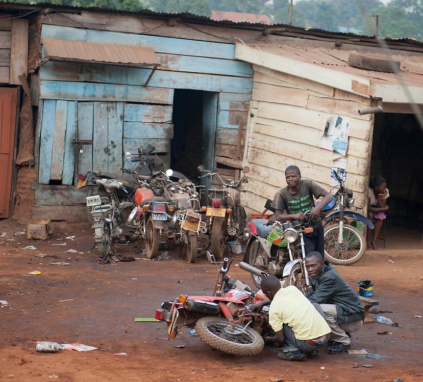 Repairing motorbikes along the street of Kampala, Uganda.