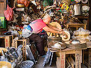 26 FEBRUARY 2016 - BANGKOK, THAILAND: A woman stacks cymbals and drums she sells on the sidewalk in the Verng Nakorn Kasem neighborhood. Verng Nakorn Kasem, also known as the Thieves' Market, was one of Bangkok's most famous shopping districts. It is located on the north edge of Bangkok's Chinatown district, it grew into Bangkok's district for buying and selling musical instruments. The family that owned the land recently sold it and the new owners want to redevelop the famous area and turn it into a shopping mall. The new owners have started evicting existing lease holders and many of the shops have closed. The remaining shops expect to be evicted by the end of 2016.      PHOTO BY JACK KURTZ