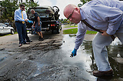Detectives Bryan McGinn, left, and Erik Noe, pull live fish out of the mud that came out of a Dodge Stratus pulled from a lake along 6th Avenue North in Naples on Thursday, April 16, 2015.  The submerged car was discovered by a crew dredging the lake.