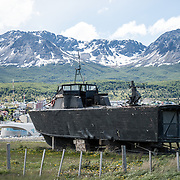 A wooden PT boat, formerly of the Argentinian Navy, the Ara Towwora, sits on the shore of Ushuaia Harbor as a naval monument.
