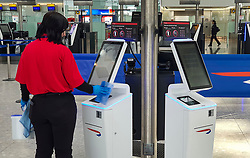 © Licensed to London News Pictures. 13/03/2020. London, UK. A worker cleans the touch screens on self check-in desks at Heathrow's Terminal 5  - which remains quiet as flights are cancelled and passengers stay at home . New cases of the COVID-19 strain of the Coronavirus are being reported daily with major sporting fixtures cancelled and people advised to stay at home for seven days if they have a cough and or a high temperature. Photo credit: Peter Macdiarmid/LNP