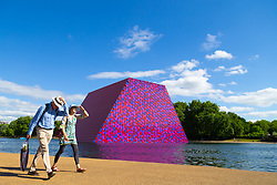A couple stride past artist Christo's 20m high installation on The Serpentine made from over 7000 barrels, titled The Mastaba, which will be on the Serpentine until 23 September 2018. The Installation is comprised of 7,506 horizontally stacked barrels. It is 20m high, 30m wide and 40m long. Hyde Park, London, June 18 2018.
