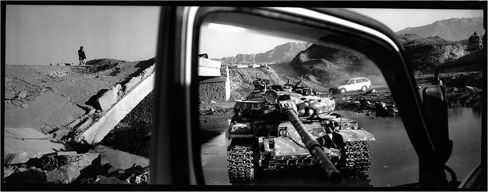 Afghanistan. Kabul. A few days after the fall of talibans, the capital is quiet. The people doesn't seem to believe what happened or maybe they became so careful with their terrible destiny. On the road of Bagram, the unique airport in working order in the North of Kabul. Bridge destroys, wreck of tank. The road remained a no man's land stuffed witth mines.