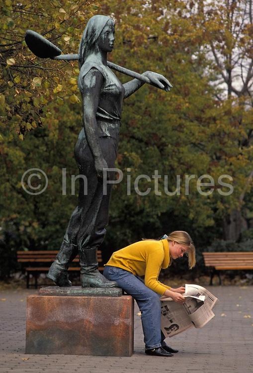 A year after the fall of the Berlin Wall and the end of the Communist Eastern Bloc, a young German woman reads a newspaper at the feet of a Trummerfrau statue honouring the rubble-clearing women after the war in Rathauspark, on 4th November 1990, in Berlin, Germany.