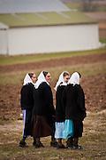 Amish girls walk across a farm field in Gordonville, PA.