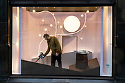 In advance of a re-opening of businesses and before a change to a Tier 2 for London during the second wave of the Coronavirus pandemic, a shop worker prepares a retailer's window on Regent Street, on 30th November 2020, in London, England. Retailers will once again be open for Christmas business on 3rd December.