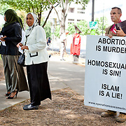A member of a fundamentalist Christian organization stands in protest during an open air prayer organized by members of the Muslim faith in Charlotte, NC.