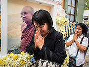 12 DECEMBER 2013 - BANGKOK, THAILAND:  A woman prays in front of a portrait of Somdet Phra Nyanasamvara during a mourning service for the revered Supreme Patriarch at Wat Bowon Niwet in Bangkok. Somdet Phra Nyanasamvara, who headed Thailand's order of Buddhist monks for more than two decades and was known as the Supreme Patriarch, died Oct. 24 at a hospital in Bangkok. He was 100. He was ordained as a Buddhist monk in 1933 and rose through the monastic ranks to become the Supreme Patriarch in 1989. He was the spiritual advisor to Bhumibol Adulyadej, the King of Thailand when the King served as monk in 1956. There is a 100 day mourning period for the Patriarch, the service Thursday, on the 50th day, included members of the Thai Royal Family. Although the Patriarch was a Theravada Buddhist, he was the Supreme Patriarch of all Buddhists in Thailand, including the Mahayana sect, which is based in Chinese Buddhism.    PHOTO BY JACK KURTZ