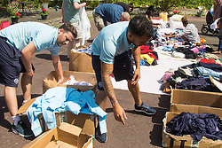London, June 14th 2017. As fire rages through a residential tower block, Grenfell Tower, in Kensington, West London, local residents show their generosity as well-wishers pour into the Maxilla Social Club with clothing, food, water and blankets for the residents of the block who will have lost everything. PICTURED: Queens Park Rangers Academy volunteers donate training kit.