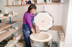 Female potter placing pot into kiln,
