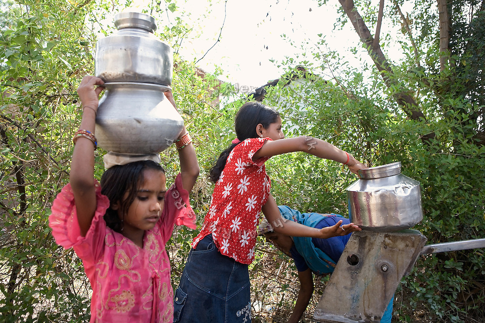 Pooja, 14, a student from the village of Pathpuri, Hoshangabad, Madhya Pradesh, India, taking part to the children's journal, a project launched by Dalit Sangh, an NGO which has been working for the uplift of scheduled castes for the past 22 years, is collecting water on a village road. Dalit Sangh is working in collaboration with Unicef India to promote education and awareness within backward communities.