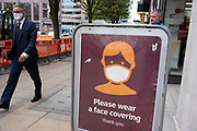 With most shops now open but with retail sales suffering due to the Coronavirus pandemic, shoppers wearing face masks at Sainsburys supermarket, which became compulsory in shops on the 24th July, in the city centre on 31st July 2020 in Birmingham, United Kingdom. Coronavirus or Covid-19 is a respiratory illness that has not previously been seen in humans. While much or Europe has been placed into lockdown, the UK government has put in place more stringent rules as part of their long term strategy, and in particular social distancing.