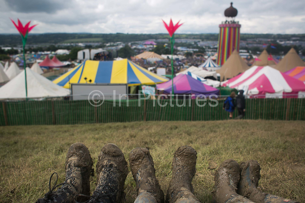 Three pairs of muddy wellies at Glastonbury Festival 25th July 2016, Somerset, United Kingdom.   The Glastonbury Festival runs over 3 days and has 3000 acts, including music, art and performance and approx. 150.000 attend the anual event.