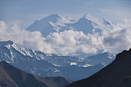 Denali becomes visible through the rolling clouds in the backcountry of Denali National Park.