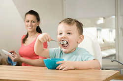 Mother and son in kitchen, smiling
