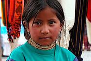 A  child poses for a portrait  at the Plaza de Ponchos  Market, Otavalo, Ecuador.