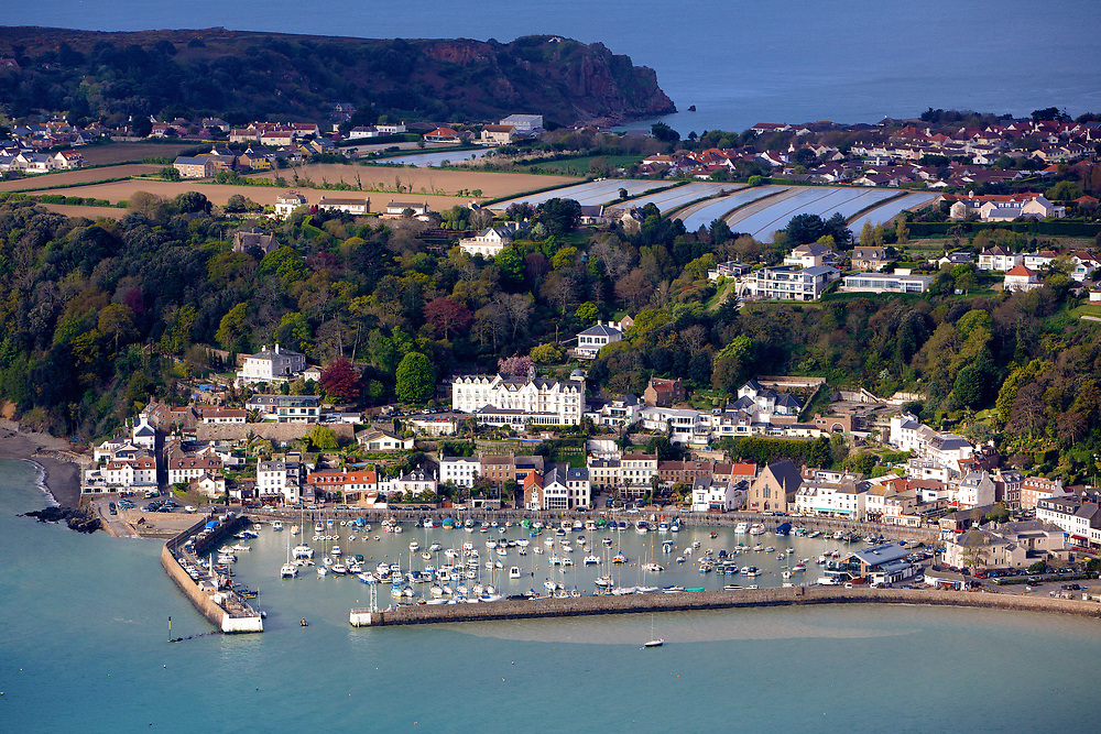 Aerial view of the boats, houses and restaurants at St Aubin's Harbour a popular tourist destination, with the countryside and fields beyond in Jersey, CI