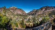 See Ouray from an overlook on the Million Dollar Highway, in Colorado, USA. Winding through the San Juan Mountains, the Million Dollar Highway is the scenic 25 miles of US Route 550 between Silverton and Ouray. It was named for the twelve miles south of Ouray through the Uncompahgre Gorge to the summit of Red Mountain Pass. As part of the San Juan Skyway Scenic Byway, the Million Dollar Highway twists along sheer cliff edges with hairpin curves and few guardrails, past spectacular yellow foliage colors in autumn. This image was stitched from multiple overlapping photos.