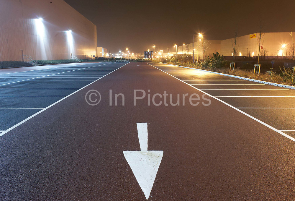 Pointing towards the viewer and the bottom of the picture near empty parking bay markings, a stencilled arrow directs traffic flow at the DIRFT warehouse logistics park in Daventry, Northamptonshire England. Bright light glows from the warehouse walls shining on to the car park creating an almost daylight landscape. This 365 acre site off Junction 18 of the M1 motorway is a hub for road, rail and service infrastructure, some 2.3m sq.ft. of distribution and manufacturing floorspace had been constructed by 2004 and occupiers including Tesco's, Tibbett & Britten plc, Ingram Micro, Royal Mail, the W.H. Malcolm Group, Eddie Stobart Ltd, Wincanton and Exel, have been attracted to this logistics location.