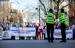 © Licensed to London News Pictures. 14/02/2019. London, UK. Two police officers keep watch as pro-Brexit protesters demonstrate opposite Downing Street. MPs continue to debate Brexit in Parliament, and will vote on a series of amendments today. Photo credit: Rob Pinney/LNP