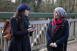 Denham, UK. 11 February, 2020. Amelia Womack (l), Deputy Leader of the Green Party, speaks to Sarah Green (r) of Save the Colne Valley at Denham Ford in the Colne Valley. Contractors working on behalf of HS2 are rerouting electricity pylons through a nearby Site of Metropolitan Importance for Nature Conservation (SMI) in conjunction with the high-speed rail link.