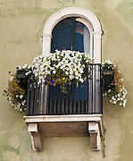 """Flower boxes bask in sun on a window balcony. Venice (Venezia) is the capital of Italy's Veneto region, named for the ancient Veneti people from the 10th century BC. The romantic """"City of Canals"""" stretches across 117 small islands in the marshy Venetian Lagoon along the Adriatic Sea in northeast Italy, Europe. The Republic of Venice wielded major sea power during the Middle Ages, Crusades, and Renaissance. Riches from Venice's silk, grain, and spice trade in the 1200s to 1600s built elaborate architecture combining Gothic, Byzantine, and Arab styles. Venice and the Venetian Lagoon are honored on UNESCO's World Heritage List."""