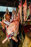 A Uyghur butcher working, The Sunday Livestock market just outside Kashgar (China's westernmost city), Xinjiang Province, China. Kashgar is along the Silk Road, near Tajikistan and Pakistan.