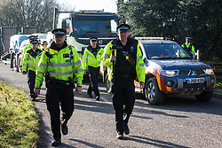 Denham, UK. 6 February, 2020. Police officers arrive to move on or arrest environmental activists from Save the Colne Valley, Stop HS2 and Extinction Rebellion who had been walking at a snail's pace along a road in order to block a security vehicle and truck delivering fencing and other supplies to be used for works associated with the HS2 high-speed rail link close to the river Colne at Denham Ford. Works planned in the immediate vicinity include the felling of trees and the construction of a Bailey bridge, compounds and fencing, some of which in a wetland nature reserve forming part of a Site of Metropolitan Importance for Nature Conservation (SMI).