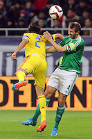 ROMANIA, Bucharest : Romania's Paul Papp (L) and Northern Ireland's Gareth McAuley (R) vie for the ball during the Euro 2016 Group F qualifying football match Romania vs Northern Ireland in Bucharest, Romania on November 14, 2014.