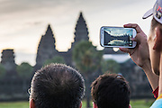 """02 JULY 2013 - ANGKOR WAT, SIEM REAP, SIEM REAP, CAMBODIA:  A tourist uses his smart phone to photograph the Angkor Wat sunrise. Angkor Wat is the largest temple complex in the world. The temple was built by the Khmer King Suryavarman II in the early 12th century in Yasodharapura (present-day Angkor), the capital of the Khmer Empire, as his state temple and eventual mausoleum. Angkor Wat was dedicated to Vishnu. It is the best-preserved temple at the site, and has remained a religious centre since its foundation– first Hindu, then Buddhist. The temple is at the top of the high classical style of Khmer architecture. It is a symbol of Cambodia, appearing on the national flag, and it is the country's prime attraction for visitors. The temple is admired for the architecture, the extensive bas-reliefs, and for the numerous devatas adorning its walls. The modern name, Angkor Wat, means """"Temple City"""" or """"City of Temples"""" in Khmer; Angkor, meaning """"city"""" or """"capital city"""", is a vernacular form of the word nokor, which comes from the Sanskrit word nagara. Wat is the Khmer word for """"temple grounds"""", derived from the Pali word """"vatta."""" Prior to this time the temple was known as Preah Pisnulok, after the posthumous title of its founder. It is also the name of complex of temples, which includes Bayon and Preah Khan, in the vicinity. It is by far the most visited tourist attraction in Cambodia. More than half of all tourists to Cambodia visit Angkor.         PHOTO BY JACK KURTZ"""