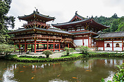 "The peaceful Byodo-In Temple reflects in a pond in Valley of the Temples Memorial Park, at 47-200 Kahekili Highway, Kaneohe, on the island of Oahu, Hawaii, USA. The Byodo-In Temple (""Temple of Equality"") was built in 1968 to commemorate the 100 year anniversary of the first Japanese immigrants to Hawaii. This Hawaii State Landmark is a non-practicing Buddhist temple which welcomes people of all faiths. The beautiful grounds at the foot of the Ko'olau Mountains include a large reflecting pond stocked with Japanese koi carp, meditation niches, and small waterfalls. Byodo-In Temple in O'ahu is a half-scale replica of the original Byodo-in Temple built in 1053 in Uji, Japan (a UNESCO World Heritage Site)."