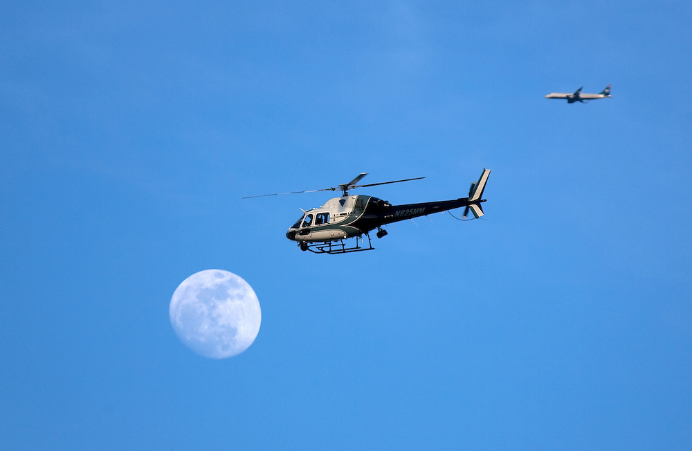 Newton, MA 03/17/2011.A State Police helicopter passes in front of the moon as it circles the scene of a shooting outside Cristofori Jewelers in Newton on Thursday afternoon..Alex Jones / For The Newton TAB
