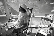 Blues and Gospel singer Pauline Goins sits on a rocking chair inside her home's screened porch with her bible.