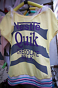"""A T-shirt with a """"Nestle"""" logo, promoting """"Checolate Malk"""" in a Chinese textile market."""