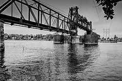 The Chicago, Burlington & Quincy Bridge is a multi-span railroad bridge built in 1898 by the King Bridge Company of Cleveland, Ohio.<br /> <br /> Overview<br /> Through truss bridge over Illinois River on Chicago, Burlington, and Quincy Railroad in Ottawa<br /> Location<br /> Ottawa, LaSalle County, Illinois<br /> History<br /> Built 1898; Lift span added ca. 1932<br /> Builder<br /> - King Bridge Co. of Cleveland, Ohio<br /> Railroads<br /> - BNSF Railway (BNSF)<br /> - Burlington Northern Railroad (BN)<br /> - Chicago, Burlington & Quincy Railroad (CBQ)<br /> - Illinois Railway (IR)<br /> Design<br /> Multi span through truss Vertical lift bridge. Three of the spans are fixed steel Pratt through trusses with pin connections. The Main Span is a Verticle Lift, Pratt through truss with pin connections. A number of timber approach spans are locted at the north and south ends of the bridge. Asher sandstone piers support each of the truss spans.<br /> Dimensions<br /> Length of largest span: 200.0 ft.<br /> Total length: 800.0 ft.<br /> Also called<br /> CB&Q - Illinois River Bridge (Ottawa)