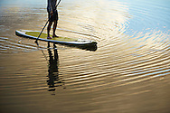 A woman drifts through calm, reflective lake water on a stand up paddle board during sunset.