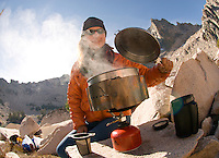 A young woman boils water for backcountry coffee while camping in the Sawtooth Mountains, Idaho.