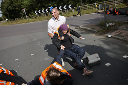 © Licensed to London News Pictures. 29/09/2021. Swanley, UK. An angry motorists drags an activist from the Insulate Britain climate change protest group as they block the road near to junction 3 of the M25 motorway near Swanley for the second time today with police on the left. 11 members of the campaign group were detained at the same junction earlier today. This is the seventh time in just over two weeks that activists have disrupted traffic on London's orbital motorway despite the government being granted a temporary High Court Injucntion banning the group from protesting on the M25. 50 protesters who were detained after Monday's protest, on junction 14 of the M25 at Heathrow, were released. Photo credit: Peter Macdiarmid/LNP