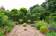 Herbaceous borders around a stone and gravel bed in the Bishop's Garden at Cothay Manor, Greenham, Wellington, Somerset, UK